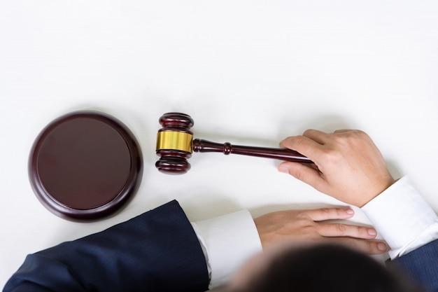Odgórny widok męski sędzia i jego ręki trzyma młoteczek przy sala sądową z kopii przestrzeniami. sprawiedliwość i prawo.