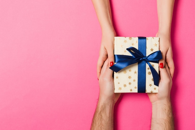 Odgórny widok mężczyzna i kobieta trzyma prezent na kolorowym tle