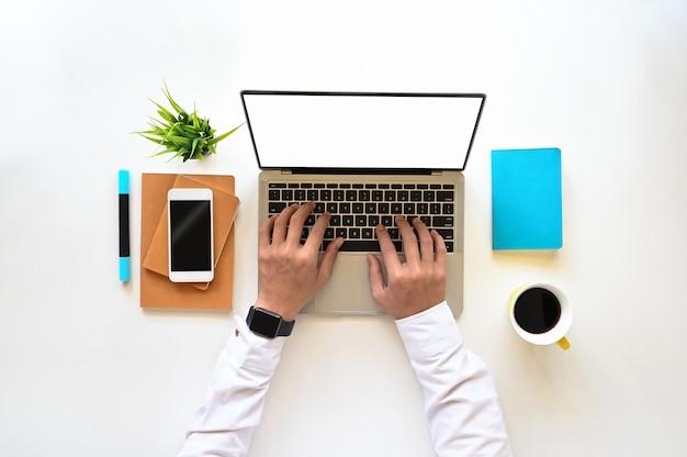 Odgórny widok mężczyzna pisać na maszynie na białym pustego ekranu laptopie na pracującym biurku w białej koszula. smartfon z czarnym pustym wyświetlaczem, filiżanką kawy, notatnikiem, pamiętnikiem i zakładaniem roślin doniczkowych.