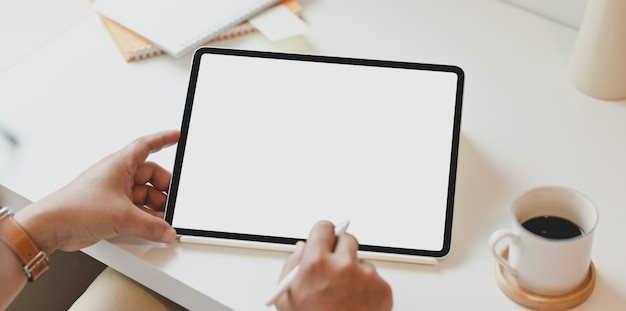 Odgórny widok mężczyzna używa pustego ekranu pastylkę w minimalnym biurze