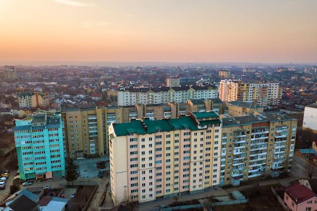 Odgórny widok miastowy miasto krajobraz z wysokimi budynkami mieszkaniowymi i przedmieście domami na jaskrawym różowym niebie przy wschód słońca kopią interliniuje tło. fotografia lotnicza dronów.