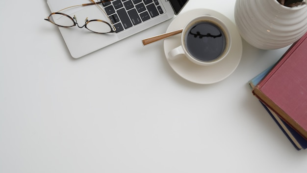 Odgórny widok miejsce pracy z laptopem, filiżanką kawy, książkami i kopii przestrzenią