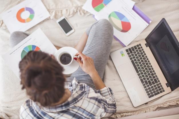Odgórny widok młoda atrakcyjna kobieta pracuje do domu przy laptopem