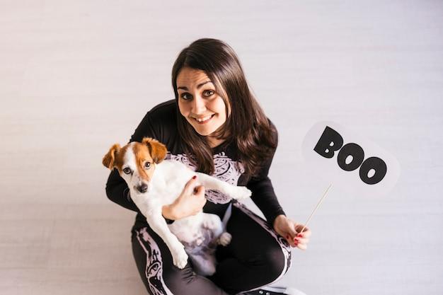 Odgórny widok młoda kobieta z jej ślicznym małym psem jest ubranym przygotowywający dla halloween. kobieta ubrana w kostium szkieletu. koncepcja halloween. wewnątrz