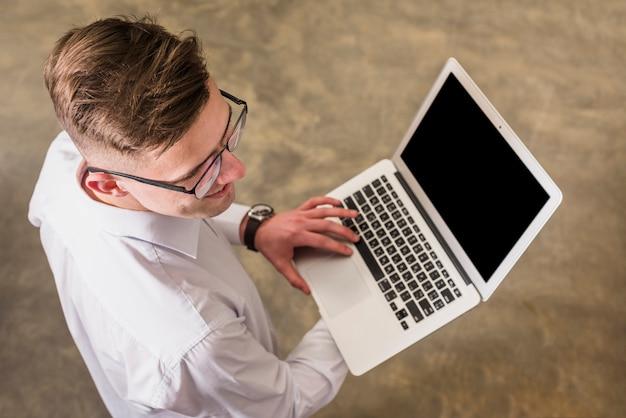 Odgórny widok młody człowiek używa laptopu mienie w ręce