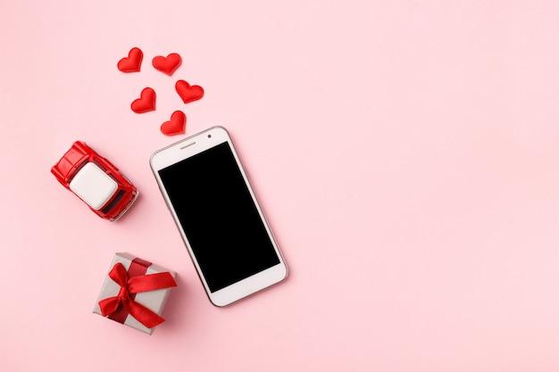 Odgórny widok mobilny telefon komórkowy i czerwoni kierowi confetti, zabawkarski samochód na różowym pastelu, copyspace. makieta szablon na walentynki. miłość, technologia. widok z góry, leżał płasko.