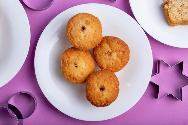 Odgórny widok muffins na białym talerzu na purpurach