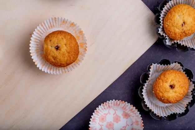 Odgórny widok muffins w papierowych foremkach na wieśniaku