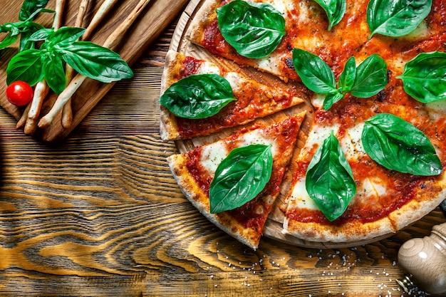 Odgórny widok na pokrojonej margarita pizzy z ingridients na drewnianym tle. mozzarella, bazylia, pomidor koktajlowy. skopiuj miejsce na projekt. zdjęcie menu, dania kuchni włoskiej