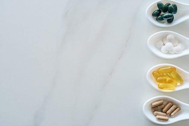 Odgórny widok naturalny witamina suplement na białej łyżce jak ramę marmurowy tekstury tło. koncepcja trendu zdrowego odżywiania.