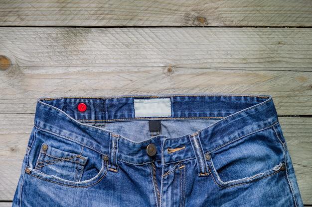 Odgórny widok niebiescy dżinsy na drewnianej powierzchni. pojęcie piękna, mody i zakupów