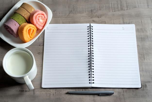 Odgórny widok notatnik, dżem rolka, filiżanka mleka, pióro na drewnianym, biznes, edukaci pojęcie i projekt
