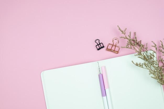 Odgórny widok notatnika materiały i kwiat na menchia stole