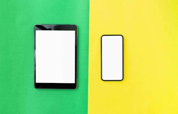 Odgórny widok nowożytna cyfrowa pastylka i smartphone na zieleni z żółtym kolorem