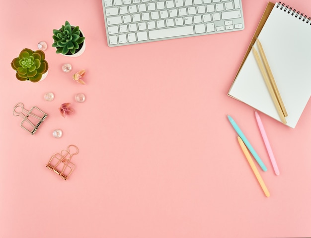 Odgórny widok nowożytnej różowej kobiety biurowy desktop z pustym notepad