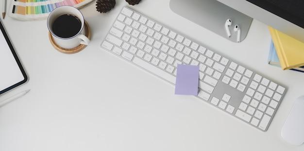 Odgórny widok nowożytny miejsce pracy z klawiaturowym komputerem i biurowymi dostawami na bielu zgłasza tło