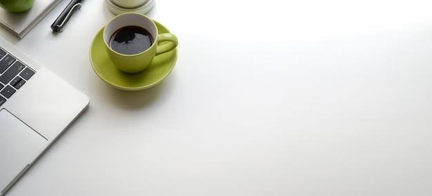 Odgórny widok nowożytny miejsce pracy z laptopem i zieloną filiżanką na bielu stole