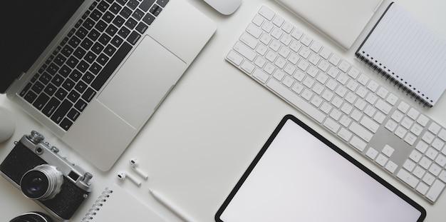Odgórny widok nowożytny miejsce pracy z laptopem, kamera, pastylka, biurowe dostawy na białym biurka tle