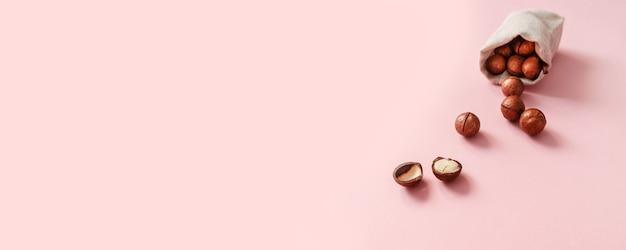 Odgórny widok organicznie macadamia dokrętki opuszczał od burlap worka i umieszcza dla teksta na różowym tle