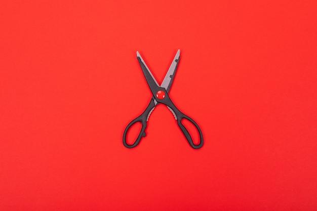 Odgórny widok otwarci nożyce odizolowywający na czerwieni