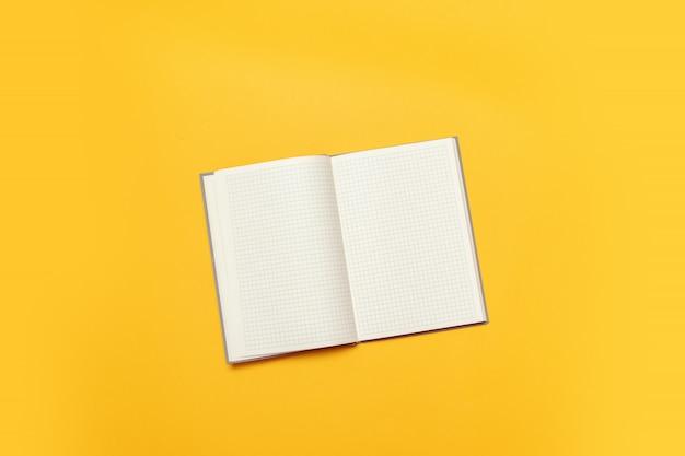 Odgórny widok otwarty pusty nutowy papier na żółtym tle. powrót do koncepcji szkoły i edukacji
