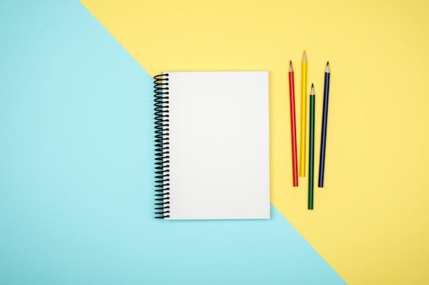 Odgórny widok otwarty ślimakowaty pusty notatnik na kolorowym biurku