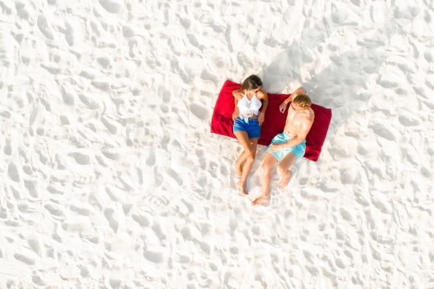 Odgórny widok pary lying on the beach na białej piasek plaży