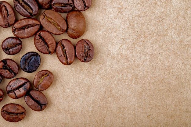 Odgórny widok piec kawowych fasoli odizolowywał brown papieru tekstury tło z kopii przestrzenią