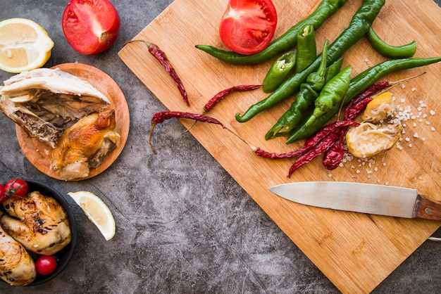 Odgórny widok piec na grillu kurczak z zielonymi i czerwonymi chilies na drewnianej ciapanie desce z nożem