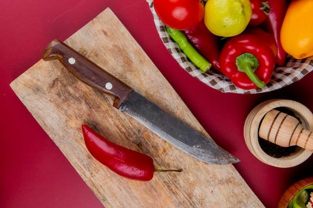 Odgórny widok pieprz i nóż na tnącej desce z warzywami w koszu i czosnku kruszarce na bordo powierzchni