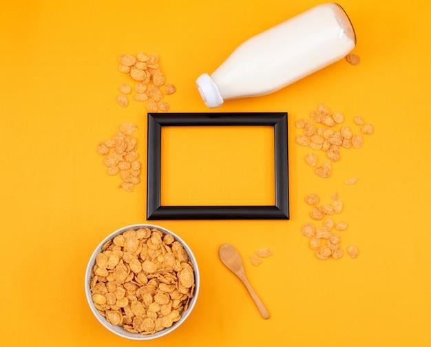Odgórny widok płatki kukurydziane i mleko z kopii przestrzenią w czerni ramie i żółtym tle horyzontalnym