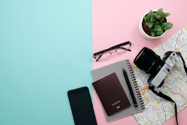 Odgórny widok podróży akcesoria, podróżnika pojęcia tło z pustym notatnikiem i kamera na pastelowym papierze.