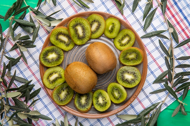 Odgórny widok pokrojona kiwi owoc na talerzu na szkocka krata obrusie