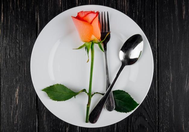Odgórny widok pomarańczowa kolor róża z łyżką i rozwidleniem na białym talerzu na ciemnym drewnianym tle