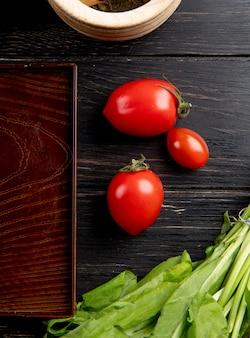 Odgórny widok pomidory i zieleni nowi liście z tacą na drewnianej powierzchni