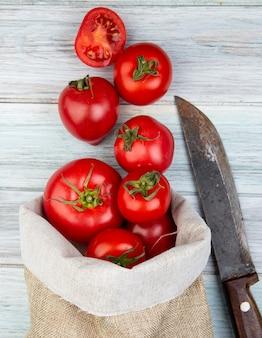 Odgórny widok pomidory rozlewa z worka i noża na drewnianej powierzchni
