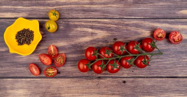 Odgórny widok pomidory z czarnego pieprzu ziarnami na drewnianej powierzchni