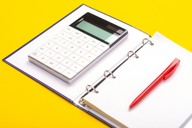 Odgórny widok pracującej przestrzeni stół z kalkulatorem, notatnikiem i piórem odizolowywającymi na żółtym tle ,.