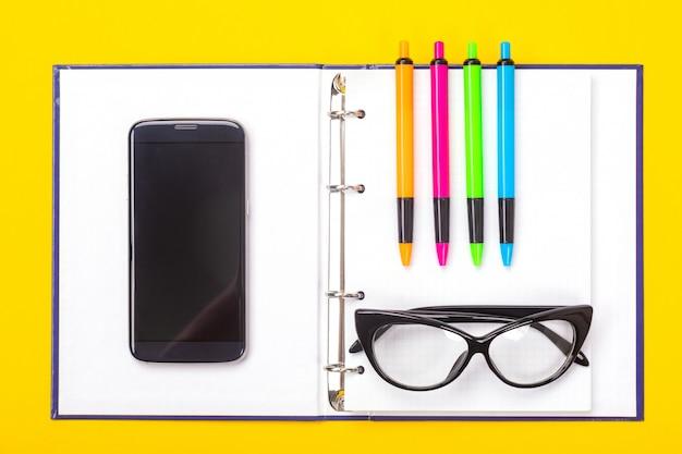 Odgórny widok pracującej przestrzeni stół z notatnikiem, szkłami i kolorowymi piórami odizolowywającymi na żółtym tle ,.