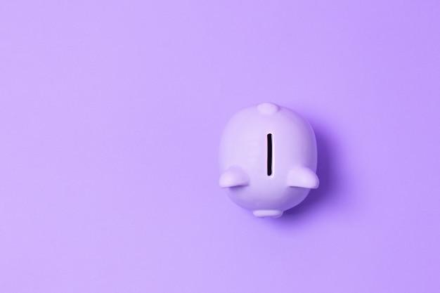 Odgórny widok prosiątko bank i savings pojęcie na purpurach tapetujemy
