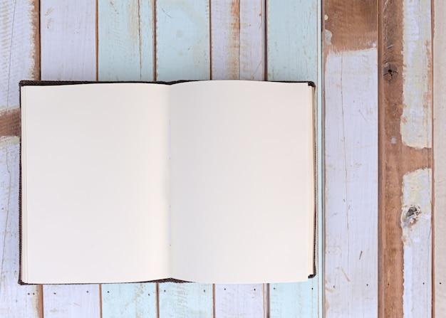 Odgórny widok przetwarza notatnika na retro drewnianej desce