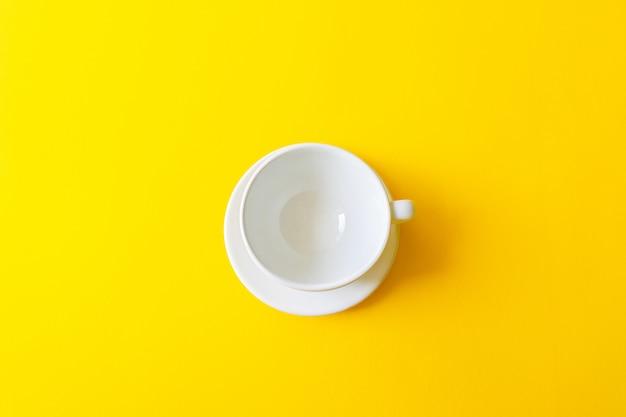 Odgórny widok pusta biała ceramiczna filiżanka na żółtej ścianie. koncepcja śniadanie rano, wypić kawę lub herbatę.
