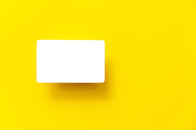Odgórny widok pusta biała wizytówka z cieniem na żółtym papierowym tle.