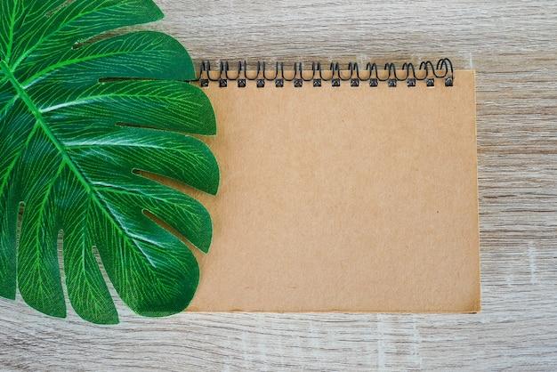 Odgórny widok puste miejsce otwarty notatnik na drewnianym biurka tle z zielonymi tropikalnymi monstera opuszcza.
