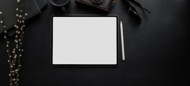 Odgórny widok pustego ekranu cyfrowa pastylka na pustym biurku w ciemnym luksusowym obszarze roboczym