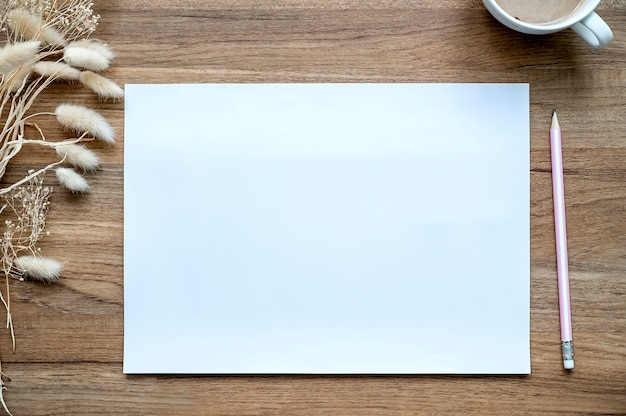 Odgórny widok pustego papieru strona na drewnianym tła biurowym biurku.