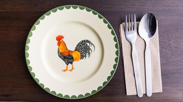 Odgórny widok pusty ceramiczny talerz z malującym kurczak ilustraci wizerunkiem.