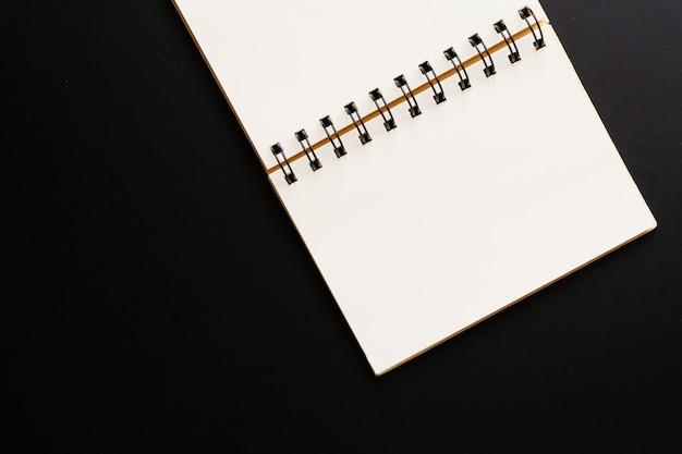 Odgórny widok pusty kraft notatnik na czerni
