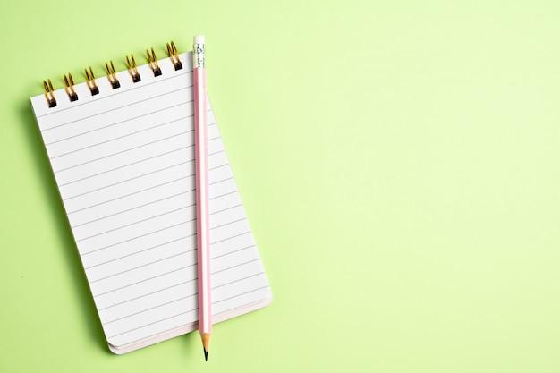 Odgórny widok pusty notatnik z różowym ołówkiem na pastelowej zieleni tle, odgórny widok, kopii przestrzeń