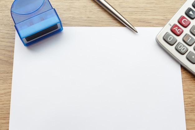 Odgórny widok pusty papier, kalkulator i pieczątka na drewnianym biurku.